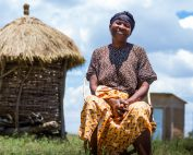 Tanzanian woman in colorful dress smiles sitting in front of a backdrop of her newly built latrine and blue skies.