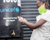 Kenyan child in green face mask washes hands at a public stand with the blue UNICEF logo. Barrel text reads 'always wash your hands with soap/ash'.